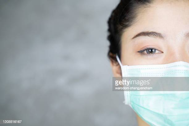 close up portrait of young asian woman with medicine health care mask against grey room background. - caretas fotografías e imágenes de stock