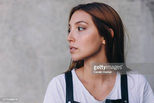 close up portrait of young hispanic woman aged 20-24 years with a serious emotion - seitenansicht stock-fotos und bilder