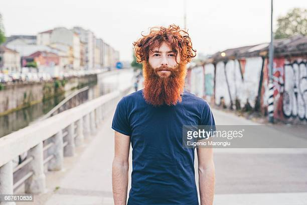 close up portrait of young male hipster with red hair and beard standing on bridge - redhead stock pictures, royalty-free photos & images