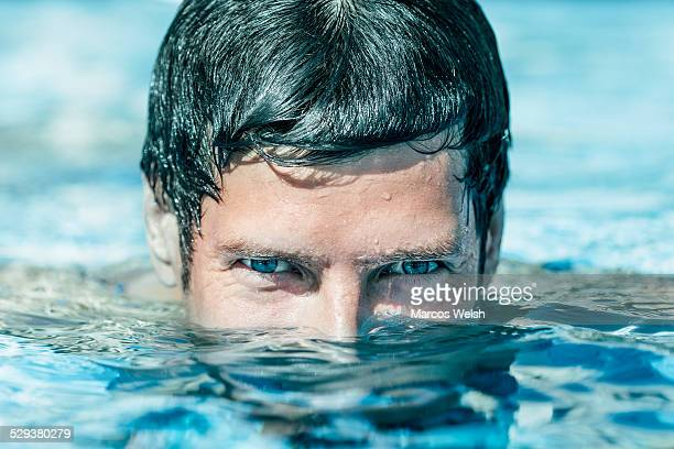 Close up portrait of young man emerging from water