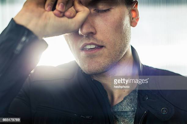 close up portrait of young man, hand on head, eyes closed - heshphoto stockfoto's en -beelden