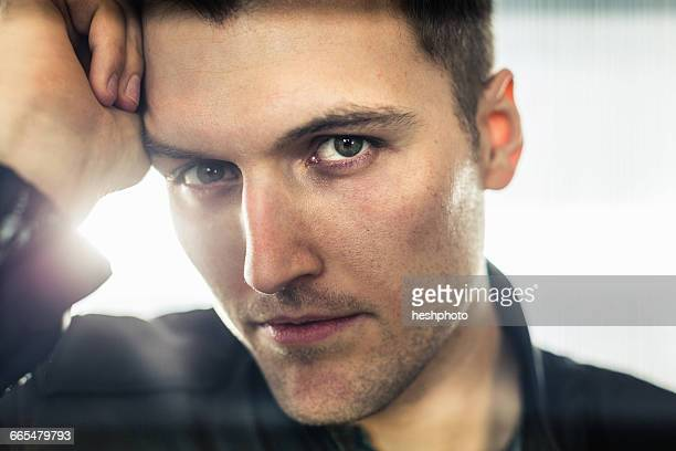 close up portrait of young man, hand on head, looking at camera - heshphoto - fotografias e filmes do acervo