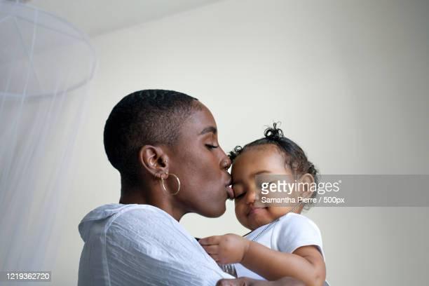 close up portrait of young mother holding baby daughter - showus imagens e fotografias de stock