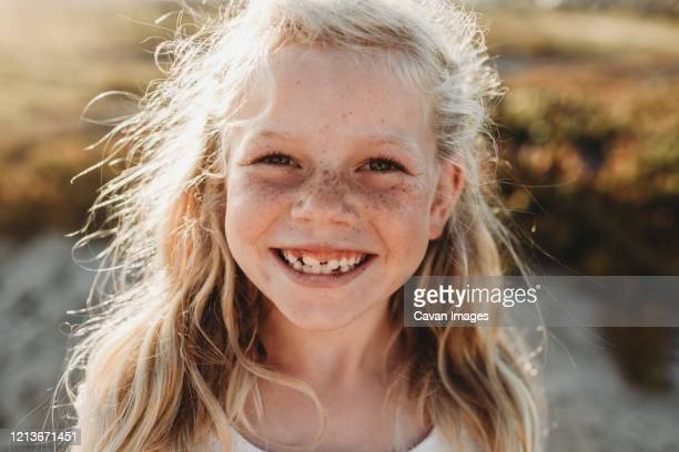 close up portrait of young school age girl with freckles smiling - childhood stock pictures, royalty-free photos & images