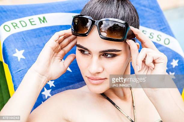 Close up portrait of young woman holding sunglasses