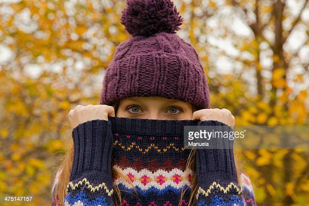 Close up portrait of young woman in park with jumper hiding face