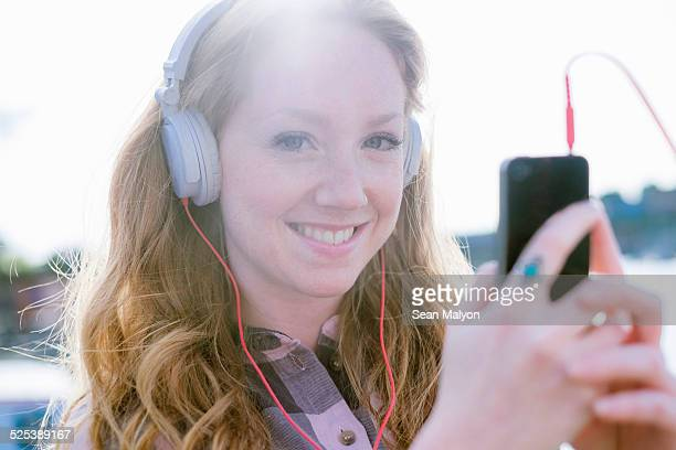Close up portrait of young woman listening to music on headphones on street