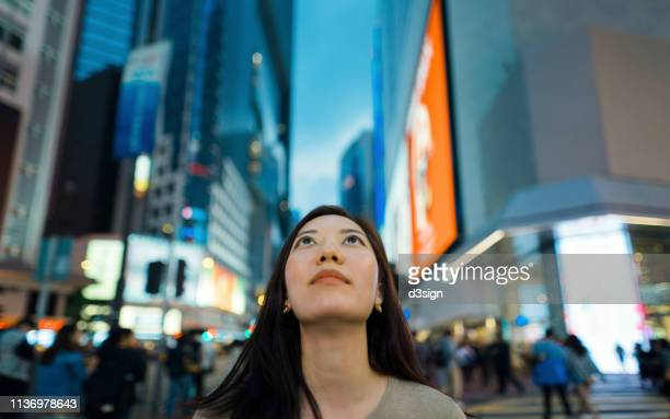close up portrait of young woman looking up to sky against urban scene in the city - ladder of success stock pictures, royalty-free photos & images