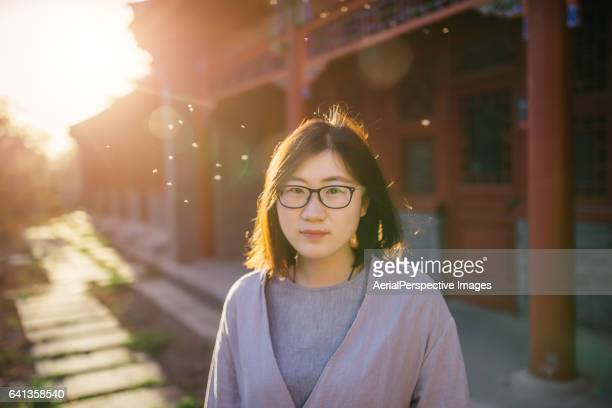 Close up portrait of young woman with a pair of glasses in Peking University, Smiling in Sunlight
