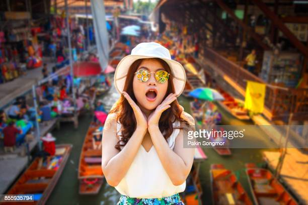 Close up portrait young asian woman beautiful girl with long red hair looking excited holding her mouth opened amazing thai culture Damnoen Saduak floating market.