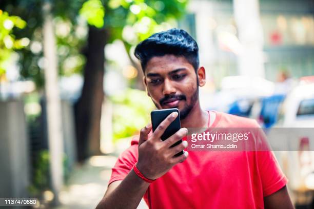 close up portraiture of young man using smart phone - omar shamsuddin stock pictures, royalty-free photos & images