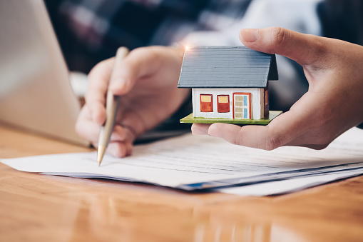 Close up real estate agent with house model hand putting signing contract,have a contract in place to protect it,signing of modest agreements form in office.Concept real estate,moving home or renting property 1130833057