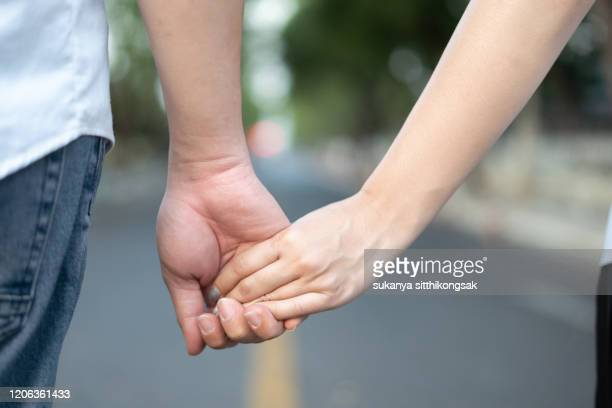 close up rear view of couples tourist hand in hand walking on the street. - 人体部位 ストックフォトと画像