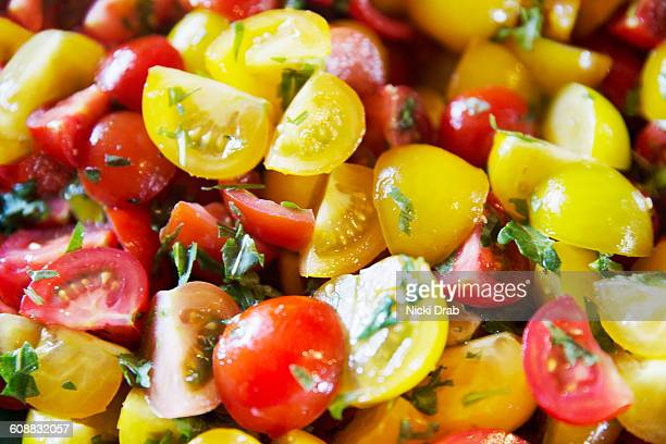 Close up red and yellow tomato salad with herbs
