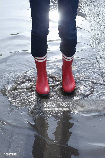 Close up rubber boots in puddle