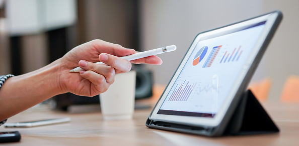 close up salesman employee hand using stylus pen to pointing on tablet screen to show company profit monthly in the meeting event at conference room , business strategy concept 1171268236
