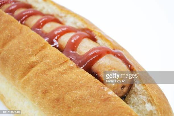 close up sausage in a bun with tomato sauce isolated on a white background - rafael ben ari fotografías e imágenes de stock