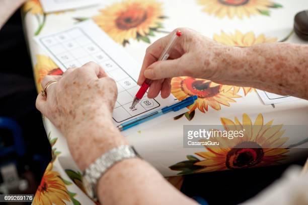 Close Up Senior Woman Hands Playing Bingo