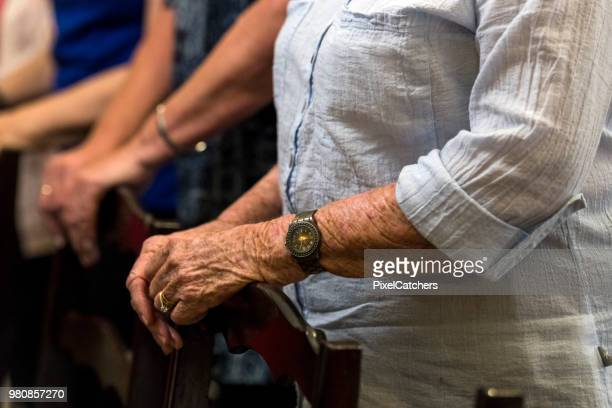 close up senior woman's hands as she rest them on the chair n front of her in quiet prayer - congregation stock pictures, royalty-free photos & images