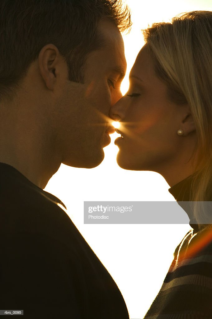 close up shot as a young adult couple lean in to kiss each other : Foto de stock