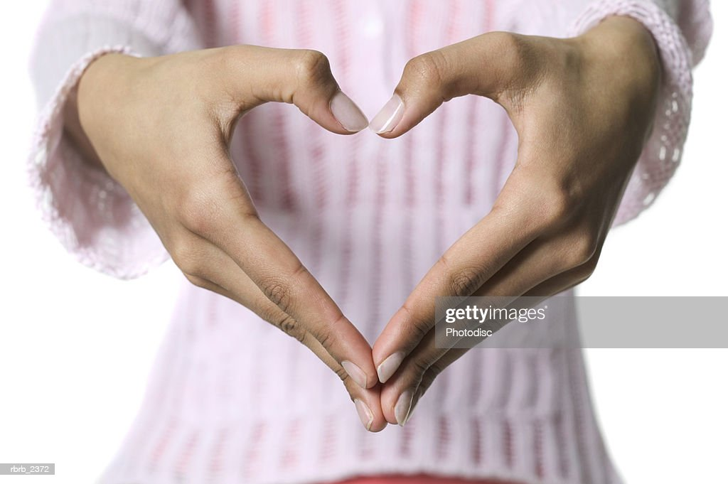 close up shot as a young woman makes a heart shape with her hands : Foto de stock