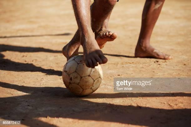 Close up shot of 2 pairs bare feet playing football