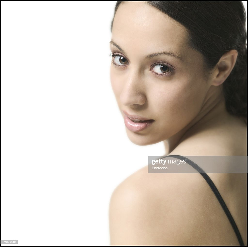 close up shot of a brunette young adult woman as she glances over her shoulder : Stock Photo
