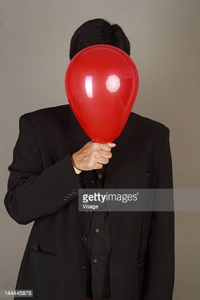 Close up shot of a businessman covering his face with a balloon