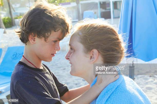 Close up shot of a little boy with brown curly hair nose to nose with his big sister who has red hair, and is laughing. She is aprox 12 yrs old and he is aprox 6yrs old. They are outside on a beach together, in beautiful light.
