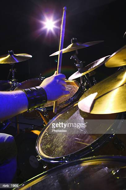 close up shot of a set of hands as they play the drums up on stage
