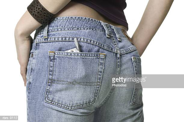 close up shot of a small cell phone in the back pocket of a teenage female