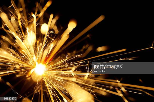 A close up shot of a yellow sparkler with black background