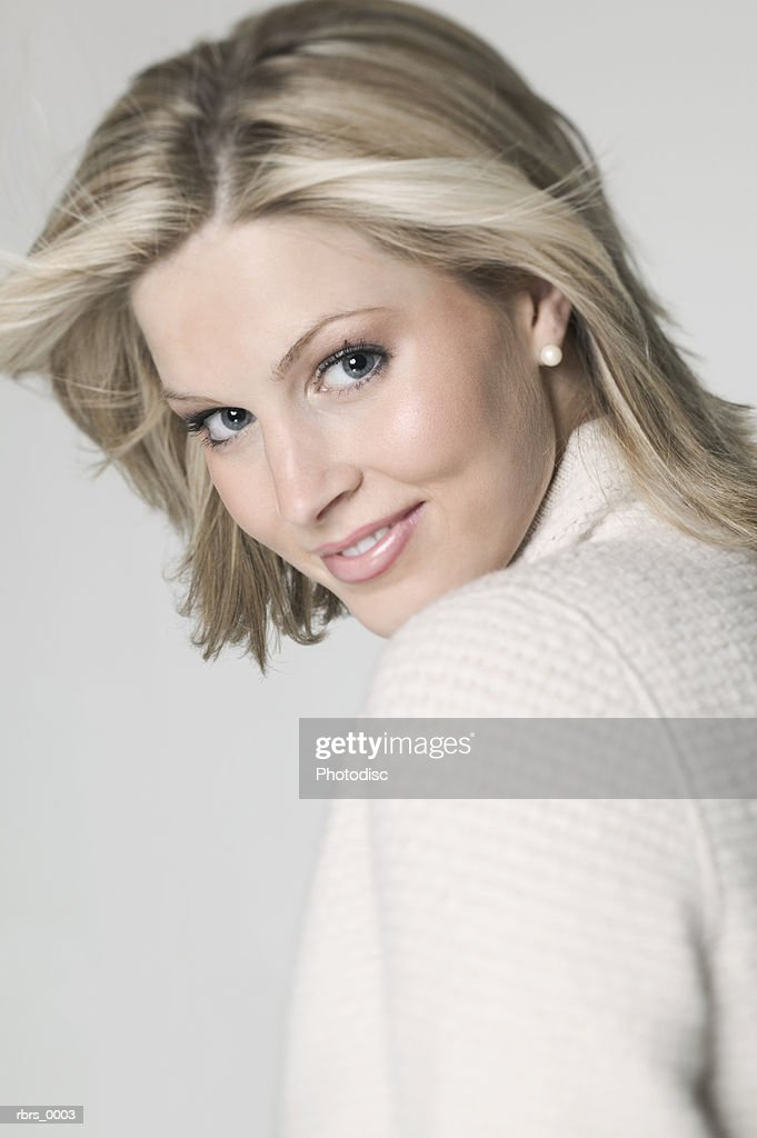 close up shot of a young adult blonde woman as she turns and smiles : Foto de stock