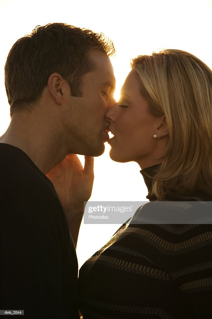 close up shot of a young adult couple as they kiss at sunset : Stockfoto