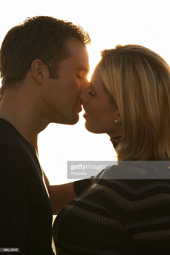 close up shot of a young adult couple as they lean in to kiss at sunset : Stockfoto