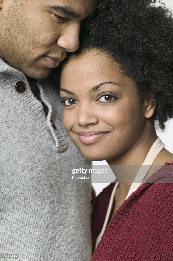 close up shot of a young adult female as she leans against her boyfriend and smiles : Foto de stock
