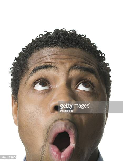 close up shot of a young adult male as he looks above his head and reacts with awe