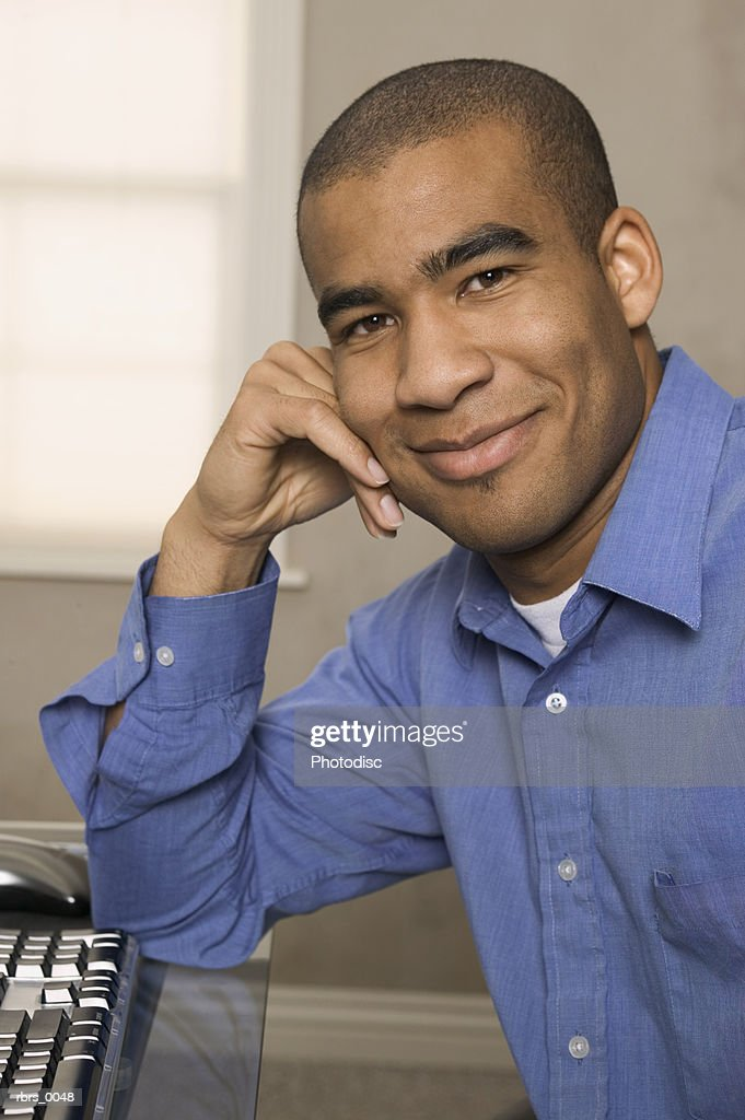 close up shot of a young adult male as he sits at his desk and smiles : Foto de stock