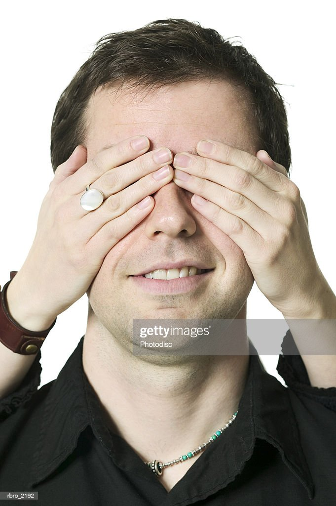 close up shot of a young adult male as his eyes are covered for a surprise from his girlfriend : Foto de stock