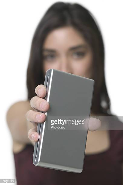 close up shot of a young adult woman as she holds out a small portable hard drive