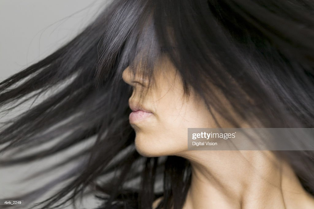 close up shot of a young adult woman as she tosses her hair around : Foto de stock