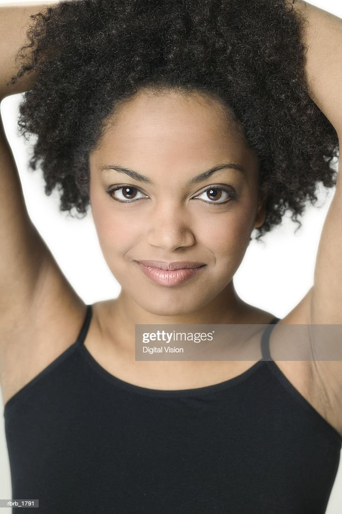 close up shot of a young adult woman in a black tank top as she puts her hands on her head and smiles : Stockfoto