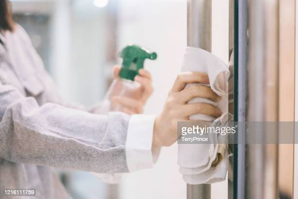 a close up shot of asian female staff cleaning a doorknob before start working in office under covid-19 epidemic - 消毒薬 ストックフォトと画像
