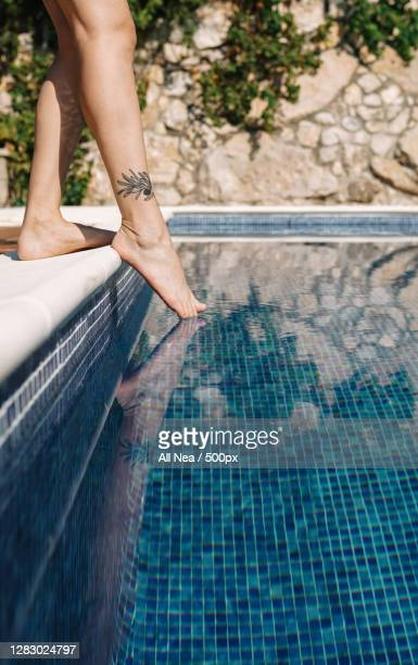 close up shot of caucasian woman dipping toes in outdoor pool,spain - 人のつま先 ストックフォトと画像