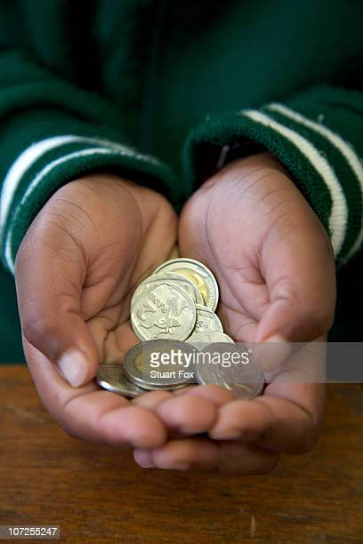 Close up shot of coins cupped in a schoolchild's hands, KwaZulu Natal Province, South Africa