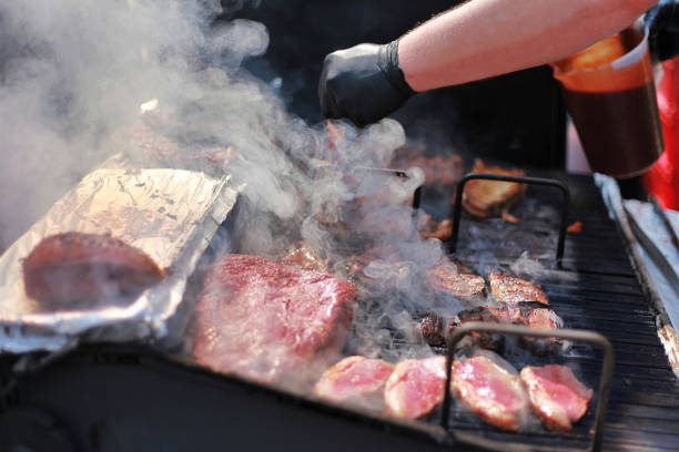 Close up shot of cook grilling smoking beef steak outdoors.