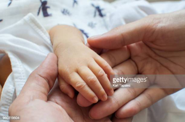 A close up shot of father and baby's hand