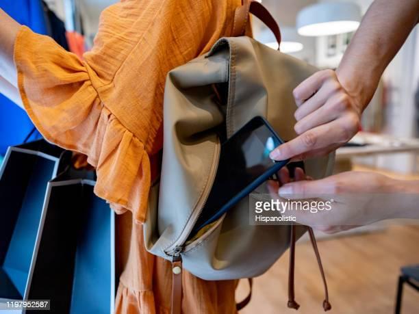 close-up shot van vrouwelijke dief proberen om een smartphone te stelen terwijl de klant kijkt naar kleren in een winkel - steel stockfoto's en -beelden
