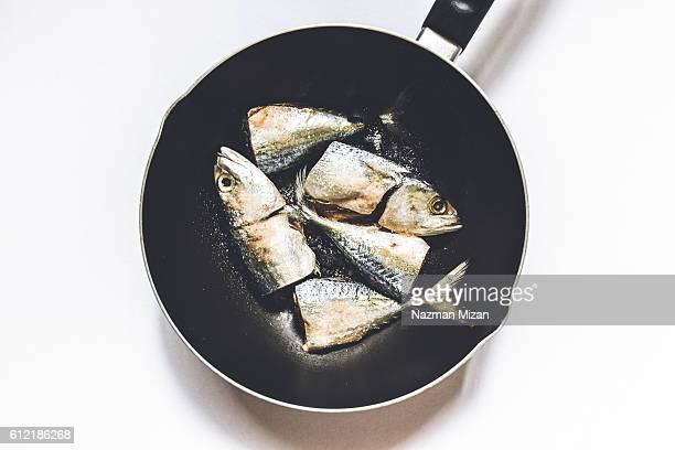 A close up shot of fish inside a frying pan.