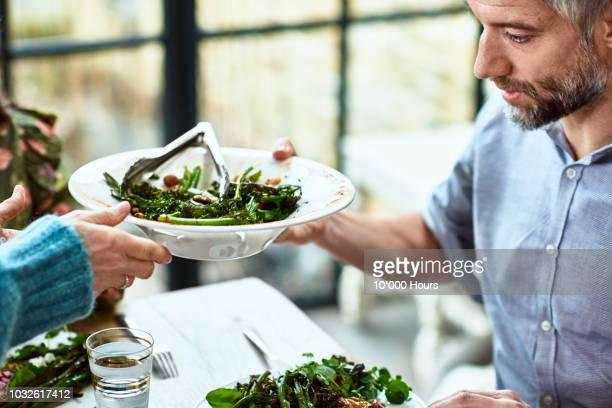 close up shot of mature man being served fresh salad - salat speisen stock-fotos und bilder